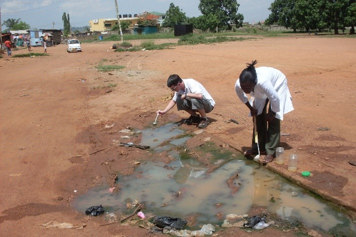 Collecting mosquito larva from pools in Ghana.
