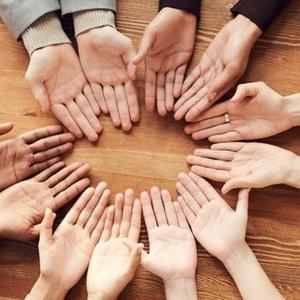 Image of many hands in a circle on a table. The hands are all facing palms up.