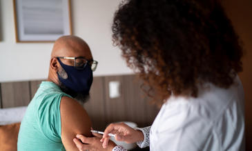 Doctor vaccinating a man wearing face mask stock photo