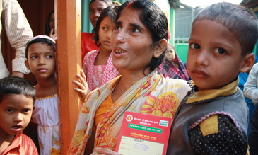 A woman with her 'red health card', which allows her to access government health services in the Korail slum, Dhaka, Bangladesh. Photo: Lucy Milmo/DFID