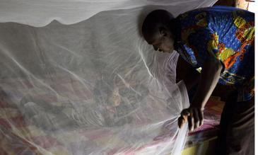 A father putting his daughter under a bednet in Burkina Faso - Photo credit: Jed Stone