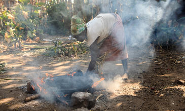 Ari tribe woman cooking injera on the open fire. Jinka, Omo River Valley, Ethiopia.