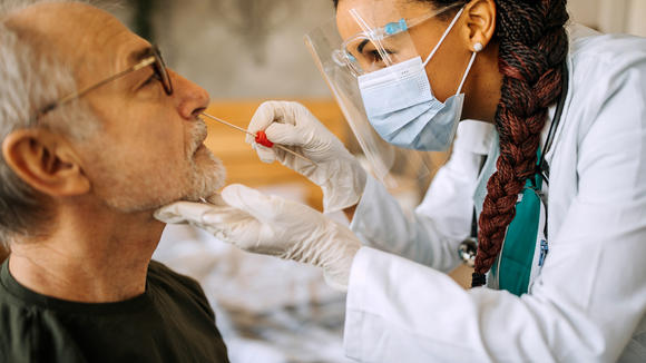 Clinician taking nasal swab from patient