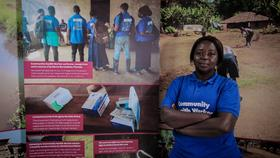 Bernadette Thomas a Community Health Worker from Bonthe District of Sierra Leone poses next to a photo exhibition about the challenges she and her colleagues face in the course of their work.